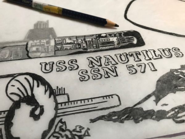 Jonpaul Smith's work in progress, linocut design. A pencil drawing of a shell, some type spelling out: USS NAUTILUS SSN 571, a submarine, and a pencil